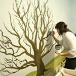 женщина рисует дерево на стене