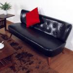 аскетичный черный кожаный диван на ножках