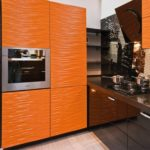 оранжевая кухня с черным холодильником