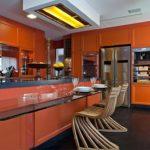 оранжевая кухня с деревянными стульями
